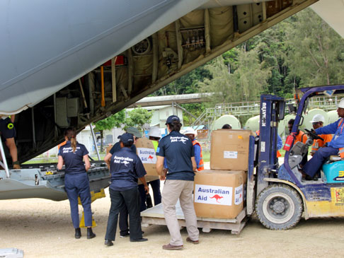 A forklift carrying boxes of Australian Aid and officials loading it into the back of an airplane.