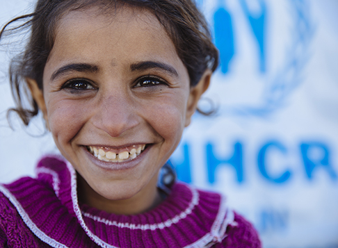 Girl smiling in front of UNHCR sign